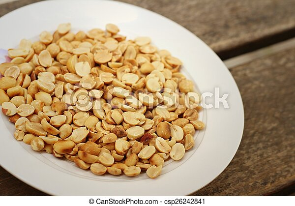 Peanuts in white plate on a wood background - csp26242841