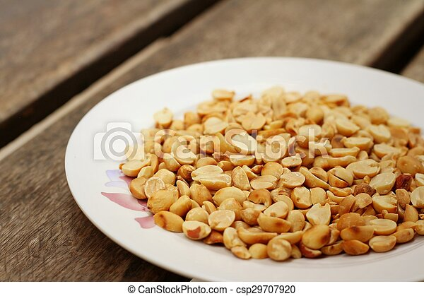 Peanuts in white plate on a wood background - csp29707920