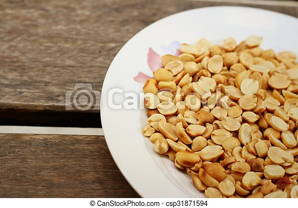 Peanuts in white plate on a wood background - csp31871594