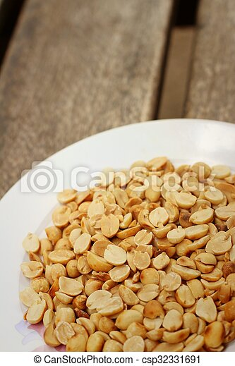 Peanuts in white plate on a wood background - csp32331691