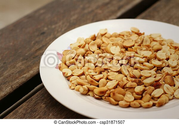 Peanuts in white plate on a wood background - csp31871507