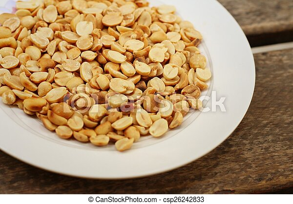 Peanuts in white plate on a wood background - csp26242833