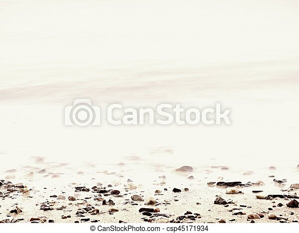 Pebbles on sandy beach against foamy sea water. Natural romantic offshore - csp45171934