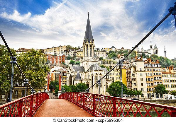 Pedestrian Saint Georges footbridge and the Saint Georges church in Lyon, France - csp75995304
