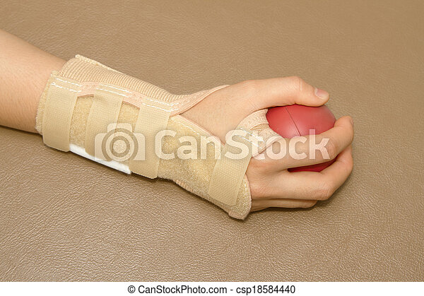 La mano de una mujer con soporte de muñeca apretando una bola suave para la rehabilitación de manos - csp18584440