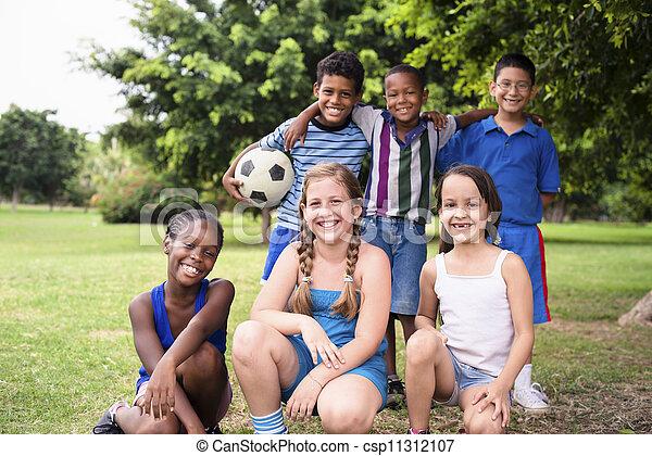 Un grupo multiétnico de felices amigos con pelota de fútbol - csp11312107