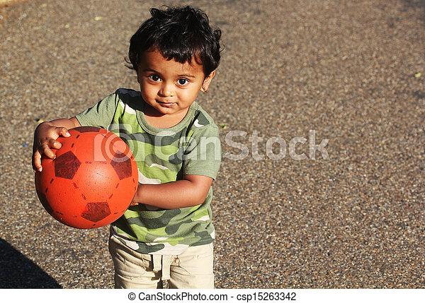 Un joven Toddler indio jugando con una bola roja en una hierba verde de un jardín o un parque - csp15263342