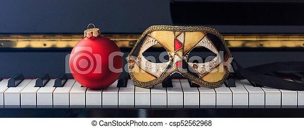 Bola de Navidad Roja y máscara de carnaval en el teclado del piano, primera vista - csp52562968