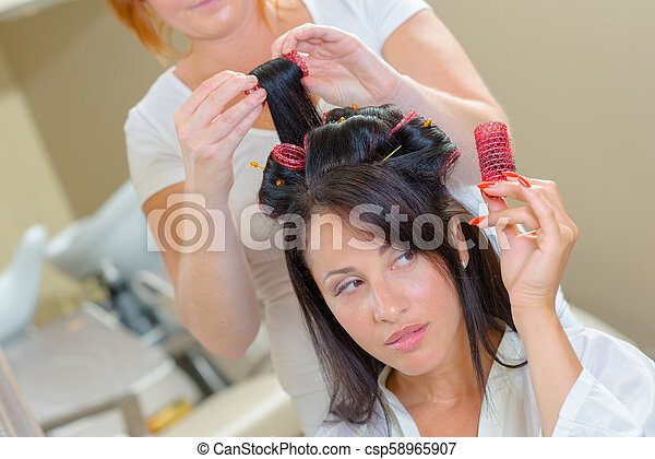 Una mujer se sentó con rodillos en la peluquería - csp58965907