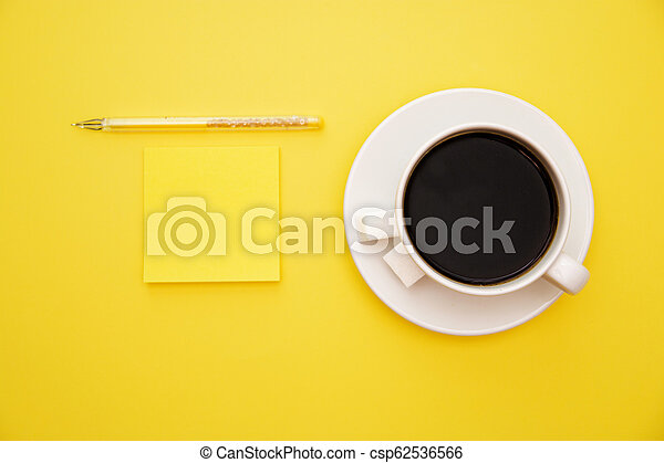 pen yellow stickers and a cup of coffee on yellow background with copy space top view - csp62536566