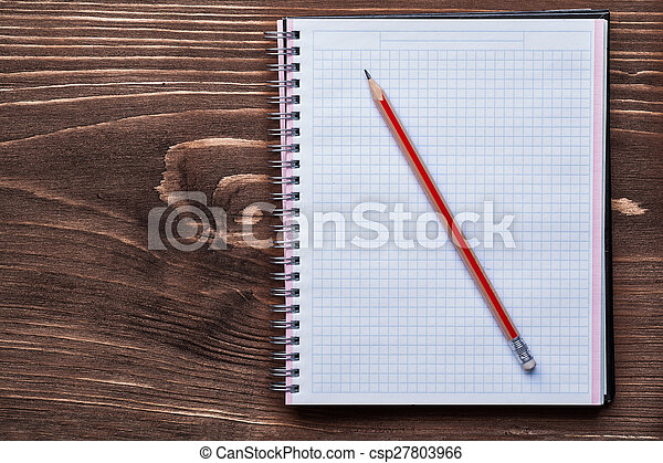 Pencil and squared notepad on pine brown wooden board office con - csp27803966