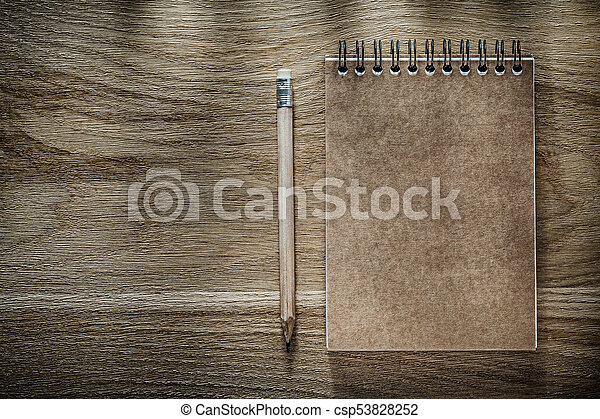 Pencil brown notebook on wooden board - csp53828252