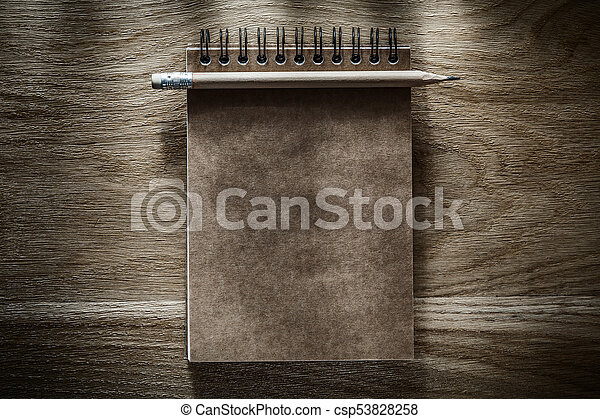 Pencil brown notepad on wooden board - csp53828258
