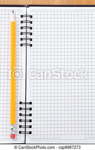 pencil on checked notebook at wood - csp9987273