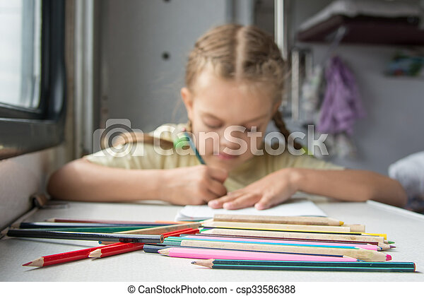 Pencils in the foreground, in the background a six year old girl drawing pencils in a second-class train carriage - csp33586388