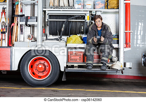 Bomba pensativa sentada en el camión - csp36142060