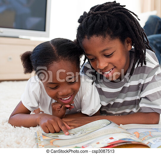 Pensive children reading a book lying on the floor - csp3087513