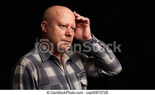 Pensive senior man. Isolated on black - csp50872729