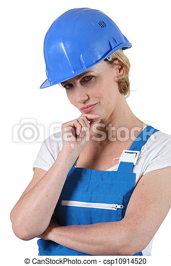Pensive woman in overalls and a hard hat - csp10914520