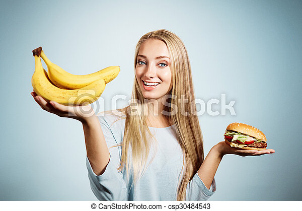 Pensive woman making decision between healthy food and fast food - csp30484543