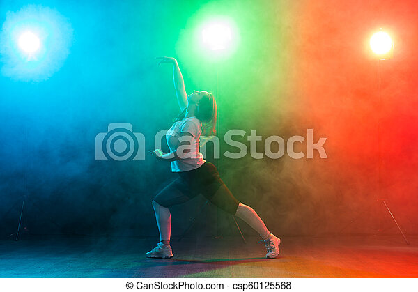 People, dancing and jazz funk concept - European young woman demonstrates  flexibility over colored background