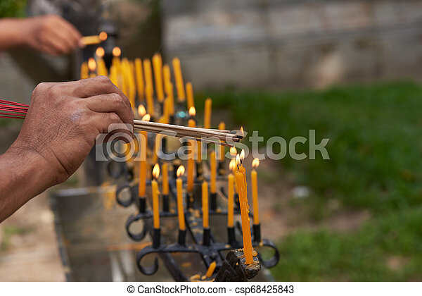 People hands burning incense from candles - csp68425843