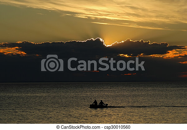 People in a boat on a sunset background - csp30010560
