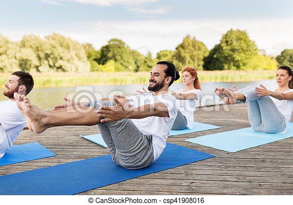 people making yoga in halfboat pose outdoors fitness