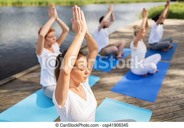 people meditating in yoga lotus pose outdoors fitness