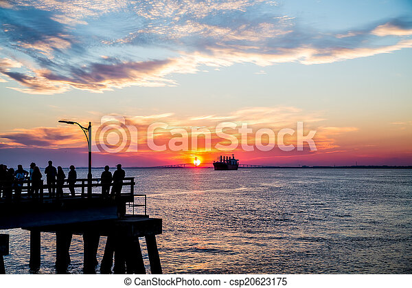 People on Pier Sillouetted with Freighter at Sunset - csp20623175