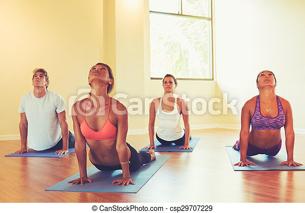 people practicing cobra pose in yoga class group of