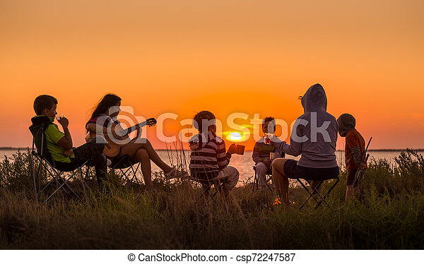 people sitting on the beach with campfire at sunset - csp72247587