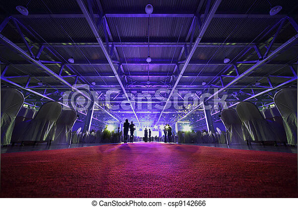 People stand, sit at table and look at light stage in party; backs of people - csp9142666