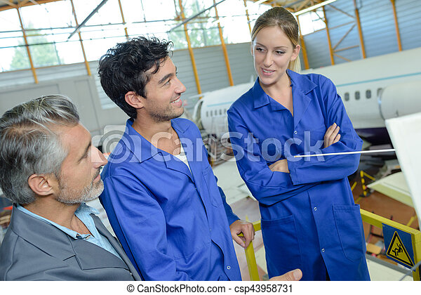 People talking in aircraft hangar - csp43958731