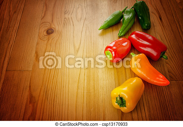Peppers on wooden background - csp13170933