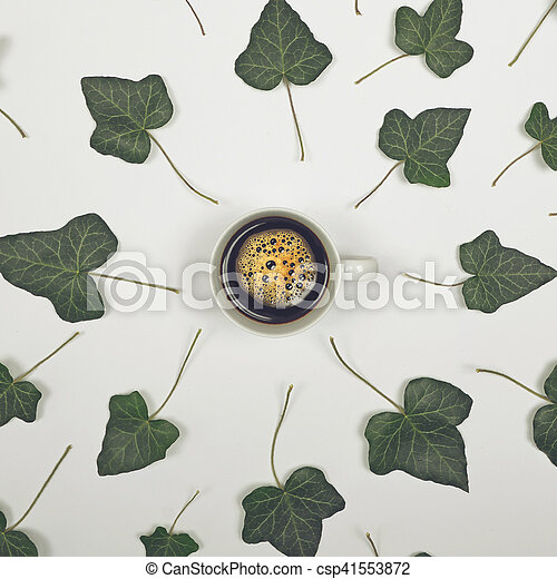Perfect cup of coffee on white background with green leaves - Flat lay design - csp41553872