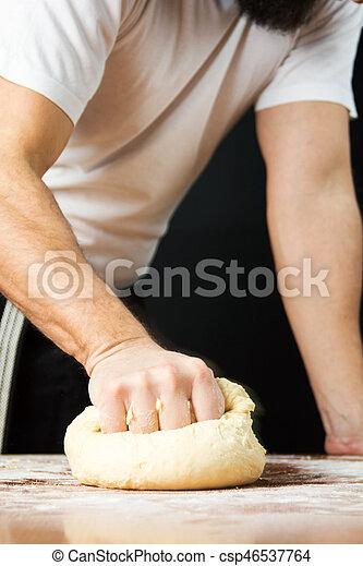 Un panadero macho golpeando la masa de la mesa - csp46537764