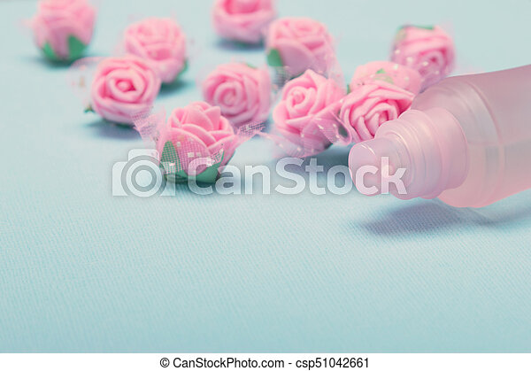 13a7a287e Perfume spray bottle with pink roses on blue textured background ...