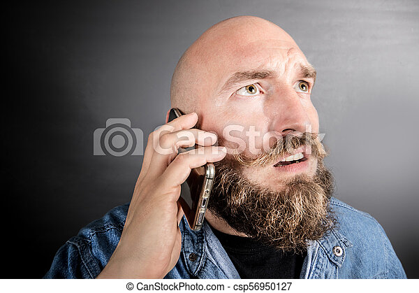 perplexed man talking on the phone - csp56950127