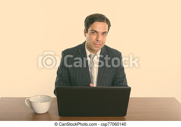 Persian businessman sitting with laptop and coffee cup on wooden table - csp77060140