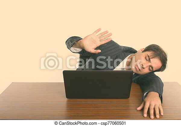 Persian businessman sleeping while showing stop hand sign with laptop on wooden table - csp77060501