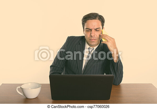 Persian businessman talking on mobile phone while using laptop with coffee cup on wooden table - csp77060026