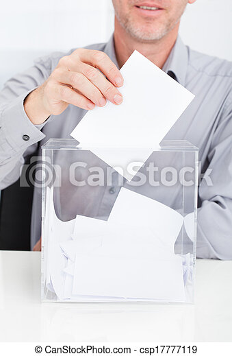 Person Inserting Ballot In Box - csp17777119