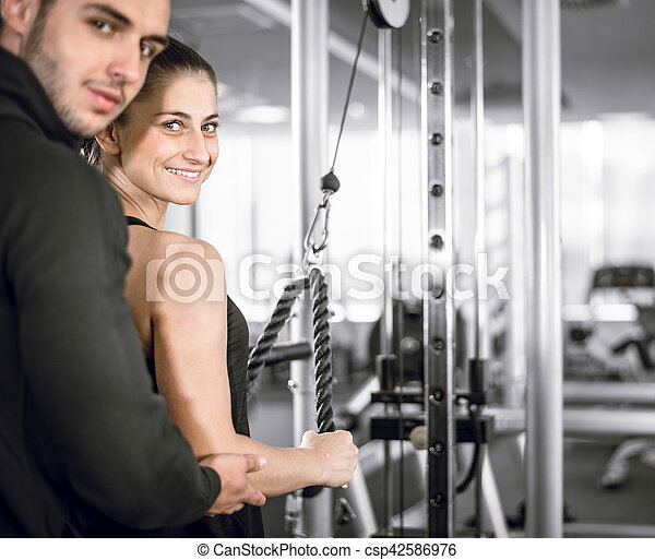 7628f9989d1 Personal fitness trainer with his client in gym. Young adult ...