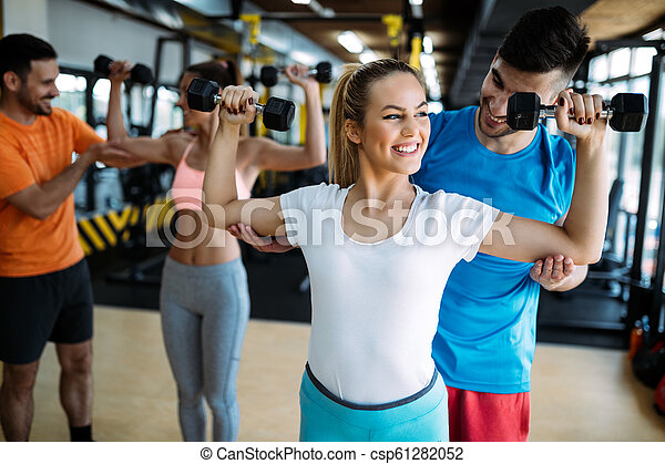 Personal trainer giving instructions in gym - csp61282052