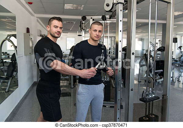 12084b4e41b Personal trainer helping client in gym. Personal trainer showing ...