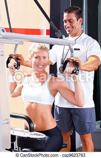 b380e185e8b personal trainer helping client in gym - csp9623763