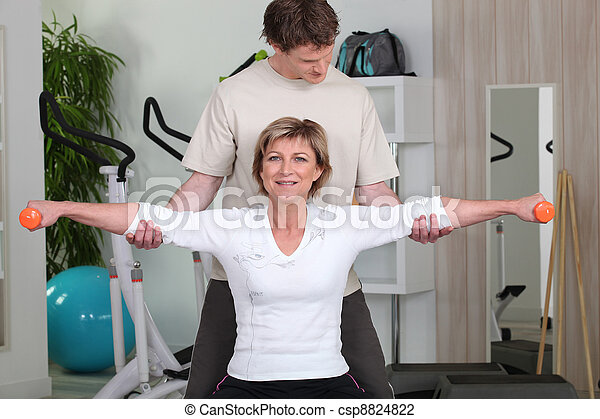 Personal trainer helping his client with her posture - csp8824822