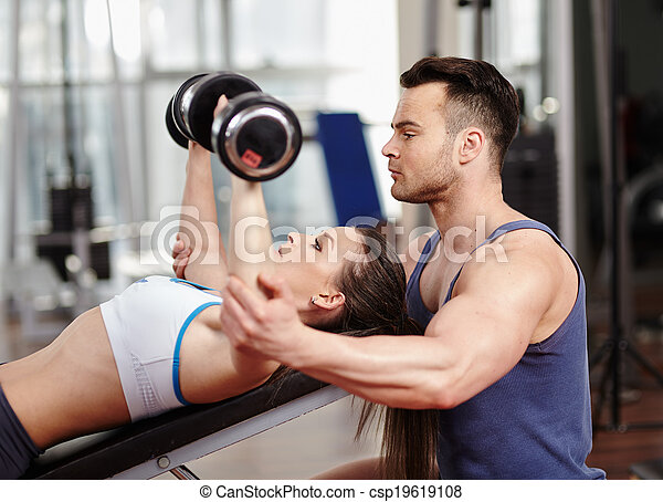 Personal trainer helping woman at gym - csp19619108