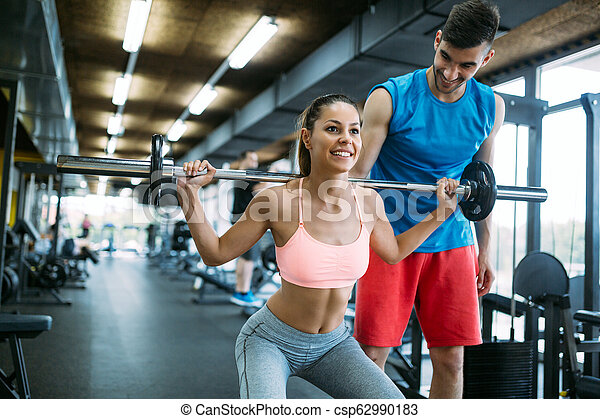 Personal trainer instructing trainee - csp62990183
